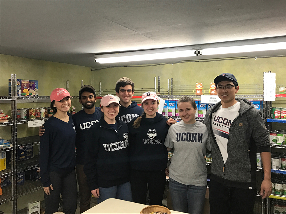 "<b>Univ. of Connecticut:</b><br><br>   <div style='font-size:18px;'>""commUNITY means helping our neighbors.""  <br><br>  For their Day of Service, UConn Stamps Scholars volunteered at the Covenant Soup Kitchen in Willimantic in an effort to support the mission: 'Realizing that people can be impoverished physically, mentally, emotionally, spiritually, socially and financially, Covenant Soup Kitchen provides food and access to basic services in an environment of care, love, support and safety to those individuals and families from the greater Windham community who come through our doors.' So, on March 25th, the UConn Stamps Scholars helped the soup kitchen stock shelves in their food pantry, organize paperwork, pack bag lunches, prepare food trays, wash dishes, and do clean-up.</div>"